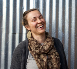 Image of a white 40 year old woman with brown hair, laughing with her eyes closed, wearing a grey sweater and gold scarf, with dangly golden earrings. Standing against a corrugated metal background.