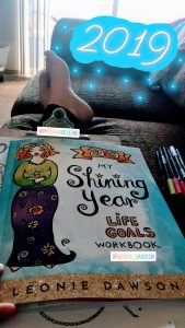 "Breana's legs and feet on the couch with a workbook in her lap titled ""My Shining Year Life Goals Workbook"" by Leonie Dawson"