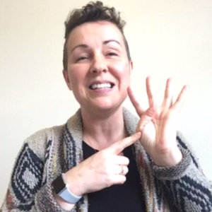 "ID: 40 year old woman with short brown hair and mulitcolored sweater, pointing to her hand in a ""4"" handshape, symbolizing the brain as it dis-integrates. Tags: interpreting during a pandemic, brain integration, interpreter, self-care, flip your lid, freak out"