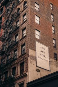 "Image of a tall brick building with fire escape stairs. Large poster on the side of the building reads, ""How are you really?"" Tag: fear self-care strategies"