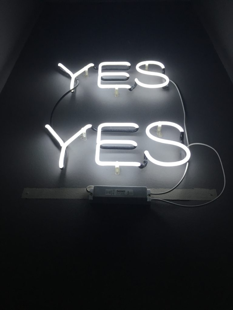 "Dark wall background with white neon sign, ""YES YES"". Tags: healthy boundaries interpreters"