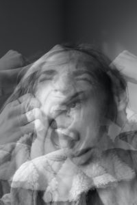 blurry black and white picture of a person wearing a shirt with a fuzzy collar holding head, closing eyes, and screaming Tag: reappraisal self-care strategies