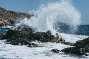 white wave crashing onto black rocks beside a mountain with blue sky behind it. Tag: tend feelings self-care strategies