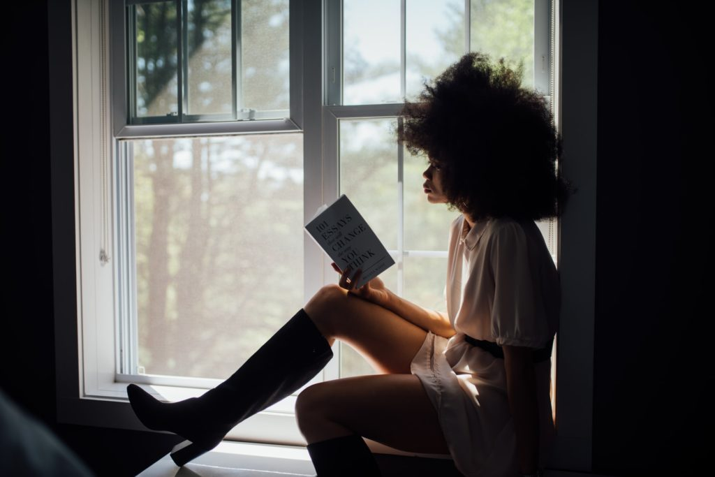 woman with curly brown hair sitting in window seat reading a book Tag: spend time self-care strategies