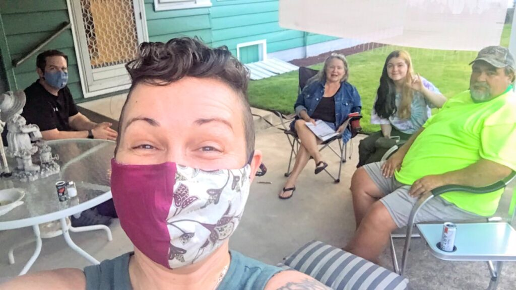 woman with short brown hair wearing a red and white floral mask on porch with table and chairs with 2 men and 2 women in the background sitting on porch chairs Tag: 2020 Thanksgiving reflection