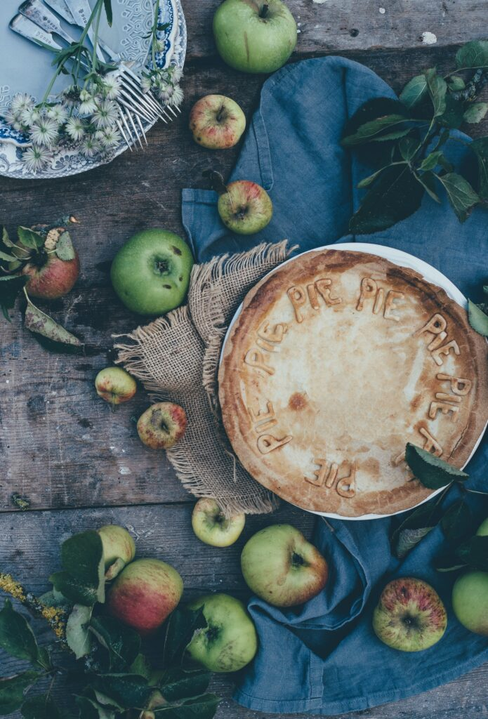 brown wood table with green and red apples, burlap and blue cloth napkins, a light blue plate with 4 forks tied together with white flowers and a brown crusted pie in a pie plate Tag: 2020 thanksgiving reflection