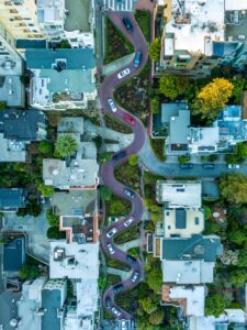 aerial view of a twisty road with cars driving the road and houses and buildings on both sides of the road with green trees scattered throughout Tag: healthy boundaries self-care