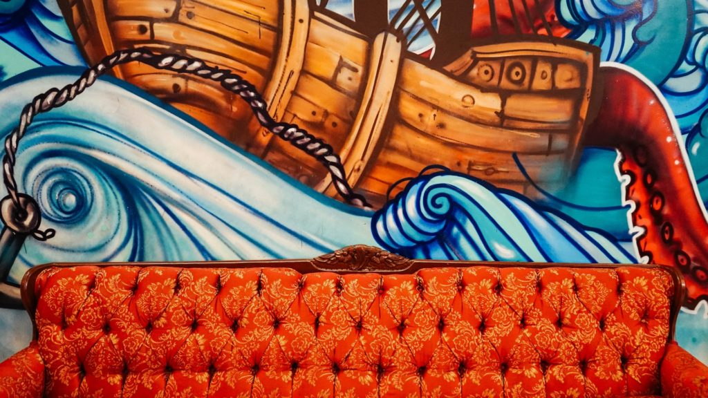 Orange mid-century sofa set in front of a brightly colored painted mural, showing a ship on top of rolling ocean waves. Tag: prayer waiting