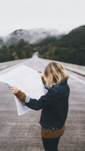 woman with blond hair wearing a brown sweater with a blue jean jacket and black pants standing in the middle of the road holding a map with green trees on the side of the road and white fog in the distance Tag: healthy boundaries self-care