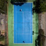 aerial view of blue rectangle tennis court with 2 people playing tennis with a green border around the tennis court and a fence around the court Tag: healthy boundaries self-care