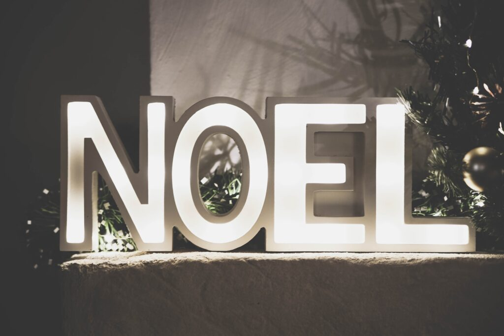 white letters spelling NOEL with green garland behind the letters and a christmas tree off to the side with gold ornaments Tag: merry everything