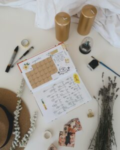 open calendar on desk with gold candles, flowers, brown straw hat, pen and marker, white sheet Tag: 2020 reflection gratitude grief