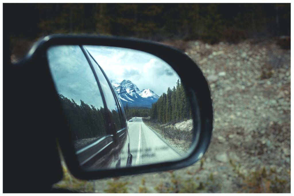 car rear view mirror showing a snow capped mountain range in the mirror with evergreen trees lining the road behind the car Tag: dear 2020