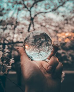 man's hand holding a glass ball with a tree with pink flowers in the background and the sunset behind the trees Tag: goodbye 2020 annual reflection