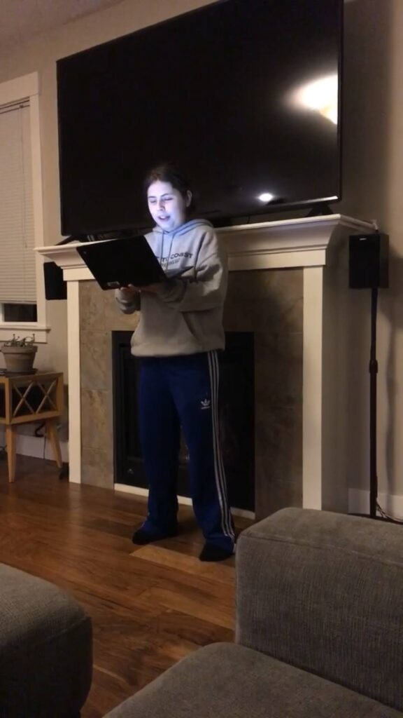 boy with gray sweatshirt and blue sweatpants standing in front of a fireplace with a tv on top holding a tablet, reading, tag: 2020 year in review