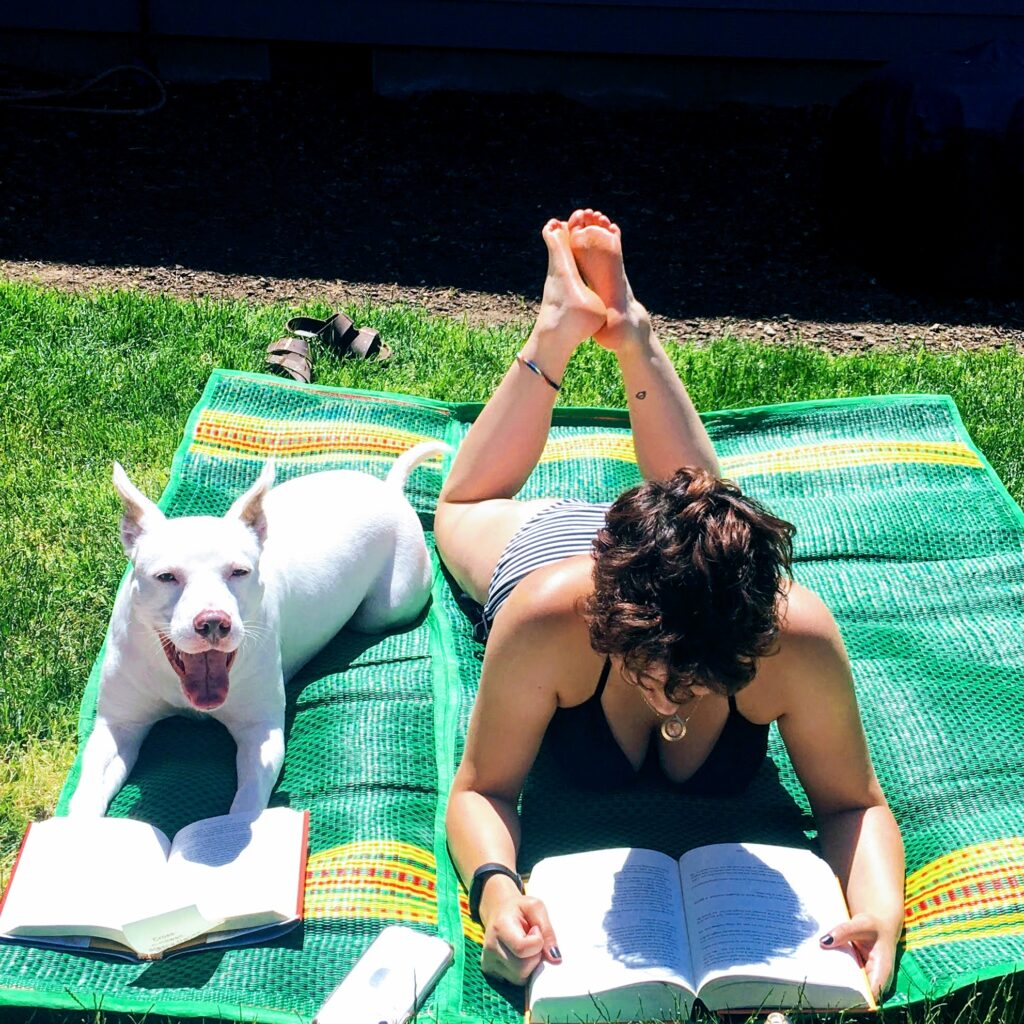 Luna, olive-skinned person with short brown hair, lying on stomach reading a book on a green mat in the grass. Next to Luna is Athena, a white Pitbull, lying on her stomach with a book in front of her, looking up at the camera. Tag: summer self-care
